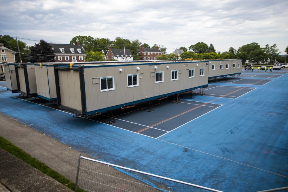 Modular units on the Fletcher tennis courts being assembled to provide extra housing for students who many need to be quarantined